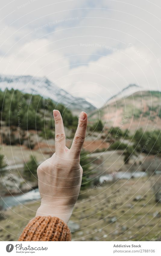 Woman showing two gesture near valley with high hills in cloudy weather 2 Gesture Valley Pyrenees Hill Clouds Lady