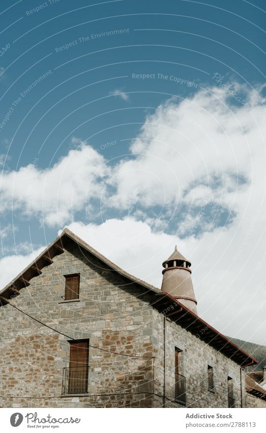 Tower near brick building and cloudy sky Brick Building Sky Pyrenees Clouds Construction Heaven Blue Height Facade Weather Beautiful Architecture Roof Exterior