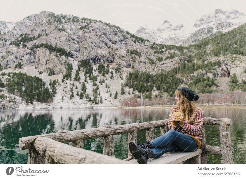 Woman on seat near wonderful lake between hills in snow Lake Hill Seat Snow Pyrenees Wonderful Water