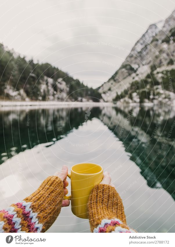 Person with cup near wonderful lake between hills in snow and cloudy sky Human being Lake Hill Snow Sky Pyrenees Clouds Cup