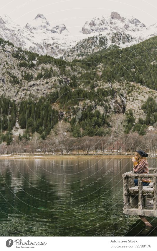 Woman on seat near wonderful lake between hills in snow and cloudy sky Lake Hill Seat Snow Pyrenees Sky Wonderful Water Surface Mountain Clouds Lady Height Tree