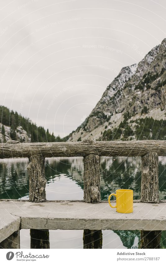 Cup on seat near wonderful lake between hills in snow and cloudy sky Lake Hill Seat Snow Pyrenees Sky Wonderful Water Surface Mountain Mug Yellow Clouds Height