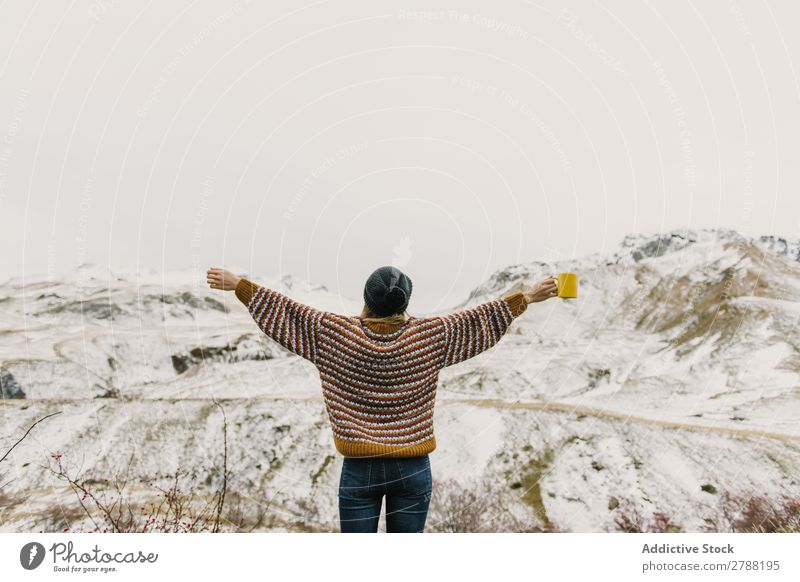 Young woman with cup and hands to sides between mountains Woman Mountain Cup Pyrenees Hand Side Lady Sweater Hat Hill Mug Snow Wonderful Youth (Young adults)