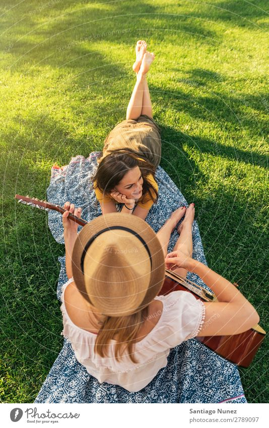 Beautiful women having fun playing guitar in the park. Woman Picnic Friendship Youth (Young adults) Park Happy Guitar Guitarist
