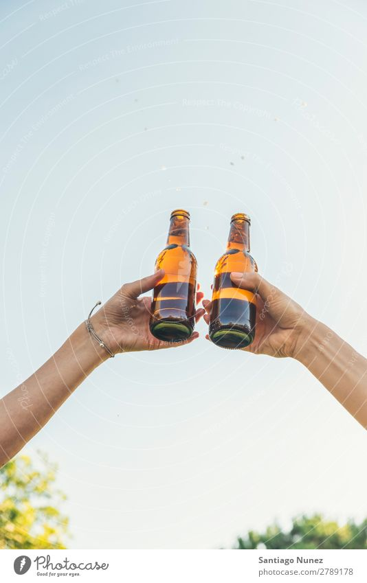 Female friends cheers clinking bottles of beer. Beer Couple Toast Cheerful Glass Bottle Hand Woman Happy Background picture Feasts & Celebrations Happiness New