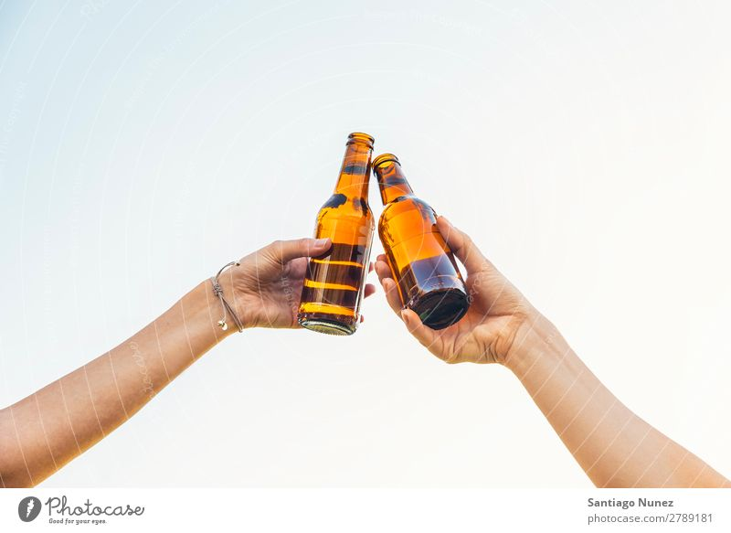 Female friends cheers clinking bottles of beer in hands. Beer Couple Toast Cheerful Glass Bottle Hand Woman Happy Background picture Feasts & Celebrations