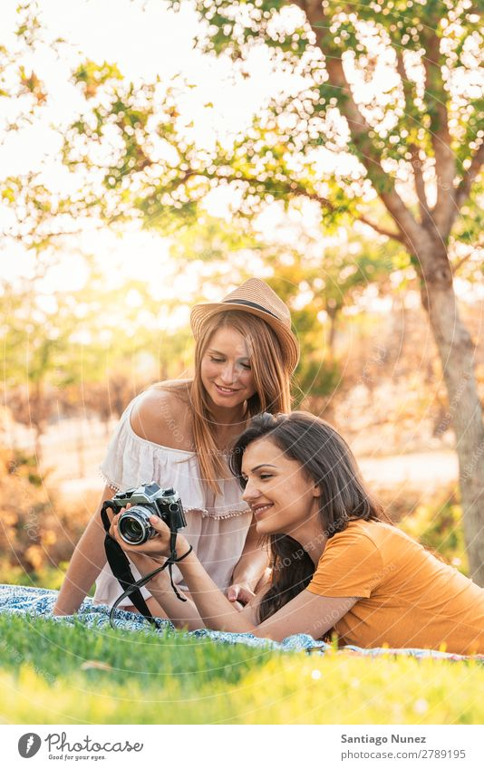 Photographer showing a picture to her friend. Woman Picnic Friendship Youth (Young adults) Park Happy Camera Guitar
