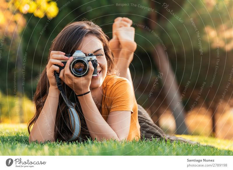 Smiling young woman using a camera to take photo at the park. Photographer Woman Photography Camera Youth (Young adults) Girl Digital White Leisure and hobbies