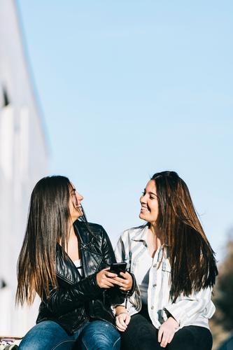 Girls using mobile phone Wall (building) Technology Adults Looking Youth (Young adults) handsome sill Teamwork American Window Sit Joy Easygoing Student