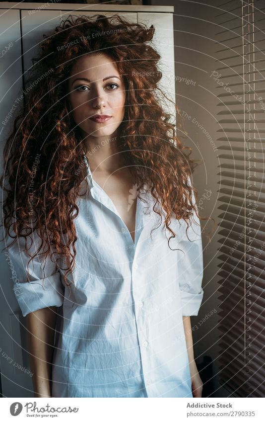 Beautiful thoughtful woman standing by a windows blind Woman Caucasian Portrait photograph Considerate Red-haired Beauty Photography Looking into the camera