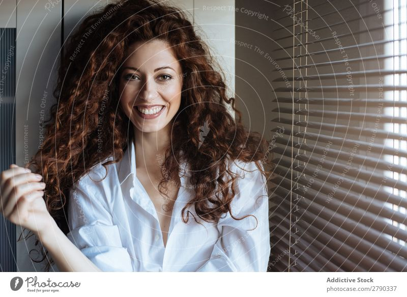 Beautiful woman standing by a windows blind Woman Caucasian Portrait photograph Smiling Looking into the camera Red-haired Beauty Photography pajamas Cute
