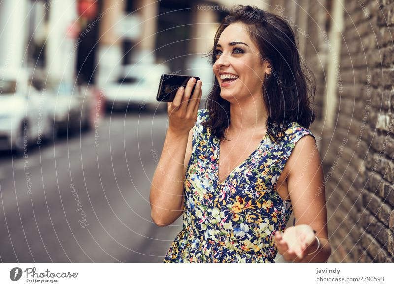 Smiling young woman recording voice note in her smart phone Woman Human being Youth (Young adults) Young woman Beautiful White Joy 18 - 30 years Street