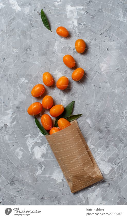 Kumquat fruits on a grey background Fruit Dessert Nutrition Vegetarian diet Diet Exotic Group Leaf Paper Fresh Natural Above Juicy Yellow Gray Colour citrus