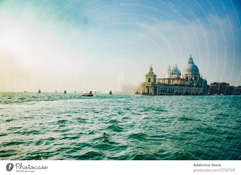 Waves on water surface and old building on shore Water Surface Building Coast Old Ocean Cathedral Sky Blue Ancient Splash Sunbeam Weather Architecture