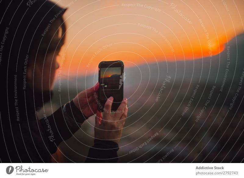 Woman shooting sunset on smartphone PDA Sunset Chechaouen Morocco Coat Lady Take