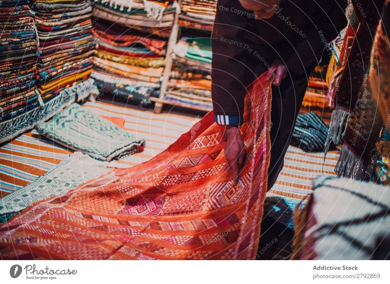 Seller showing carpet in market seller Carpet Indicate Gift Red choice Pick Markets East Bazaar Tradition Shopping Storage Tourism Multicoloured Chechaouen