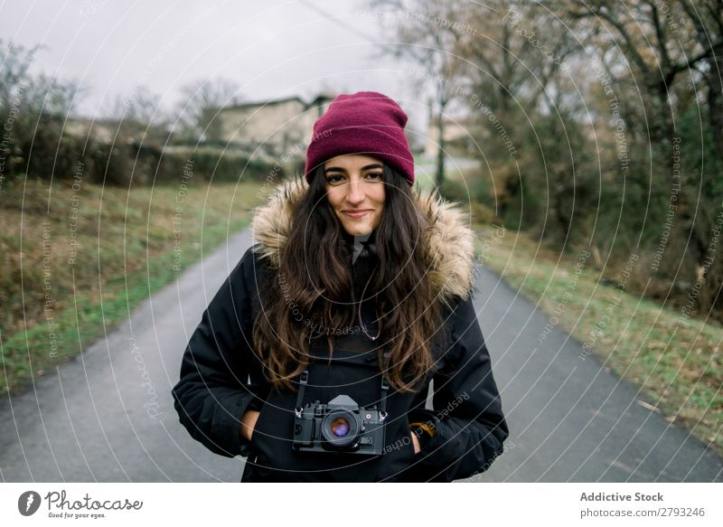 Smiling woman in coat with camera Woman Camera Landscape Coat orduna Spain Lady Hat Hand pocket Cheerful Wear Winter Attractive Youth (Young adults) Street