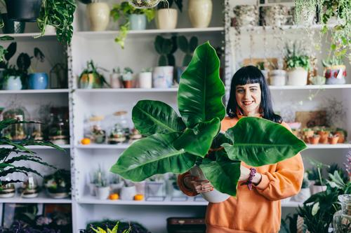 Woman holding big plant in the flower shop. Flower Shopping Happy Work and employment Plant Hold Pot Green Floral Business Smiling Florist Retail sector Natural