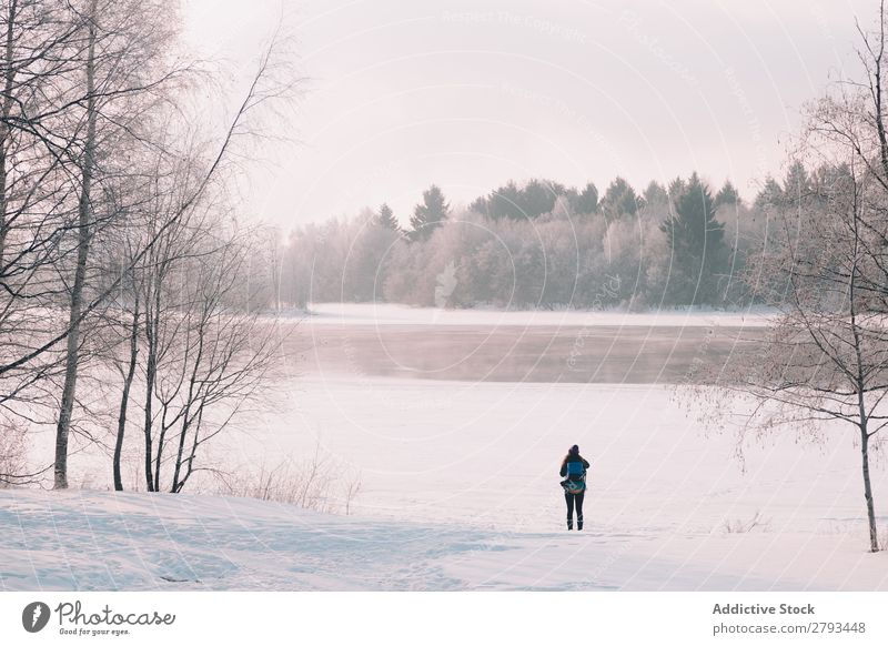Anonymous woman standing near river in snowy countryside Woman Winter Landscape River Frozen Snow The Arctic Cold