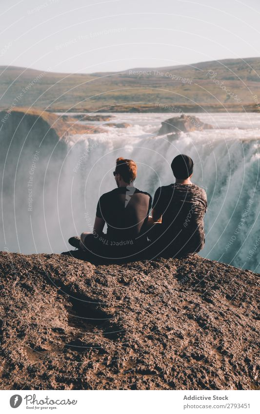 Anonymous men looking at waterfall Man Waterfall Cliff Vantage point Nature Landscape The Arctic