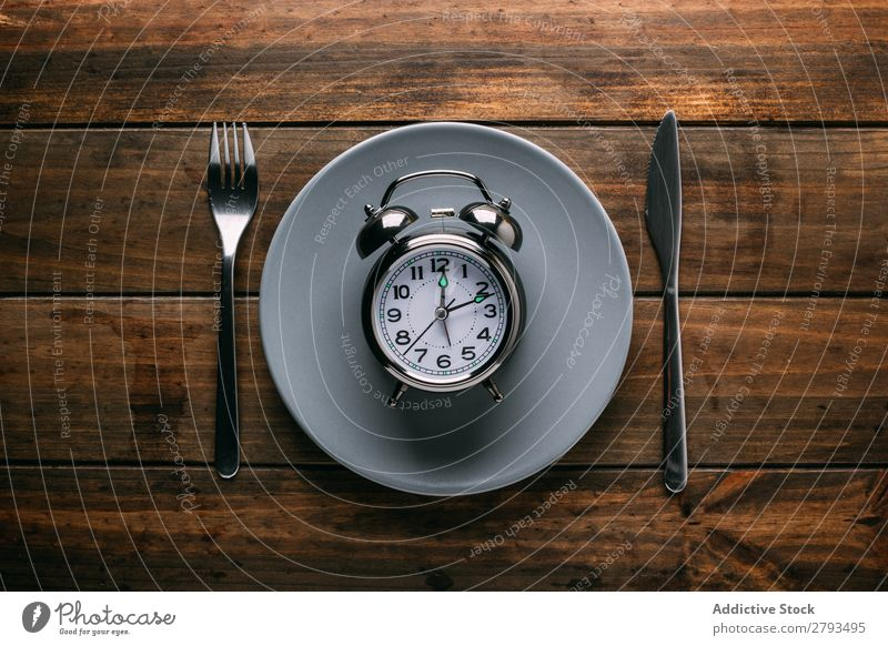 Cutlery near plate with alarm clock Plate Alarm clock Table Conceptual design Diet Fork Knives Time Meal Minute hand Hour hand Lunch Dinner Breakfast Mechanical