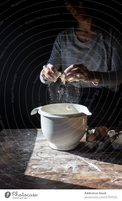Person cracking egg in bowl on table Egg Bowl Cooking Table Flour Wood Meal Craft (trade) To break (something) Tasty Human being Bread Baked goods Cake Bakery