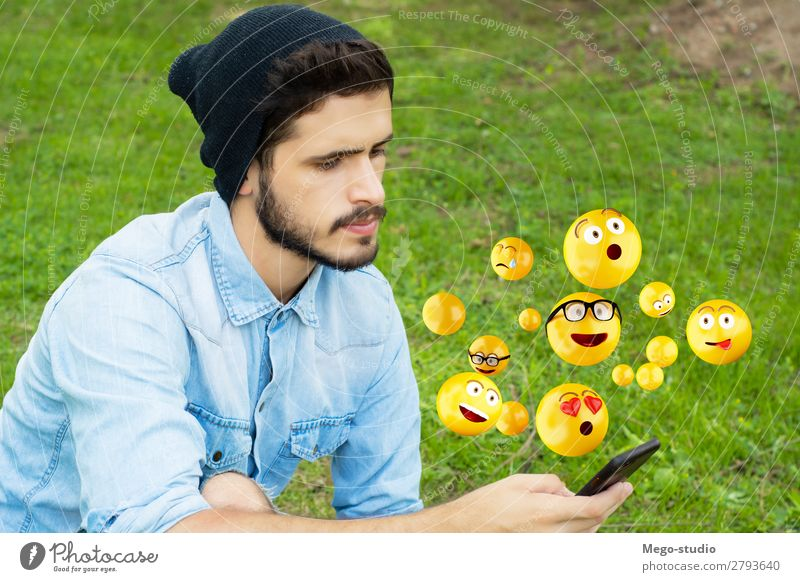 Young man using smartphone sending emojis. Lifestyle Happy Face Telephone PDA Screen Technology Internet Human being Man Adults Hand Funny Modern Smart Emotions