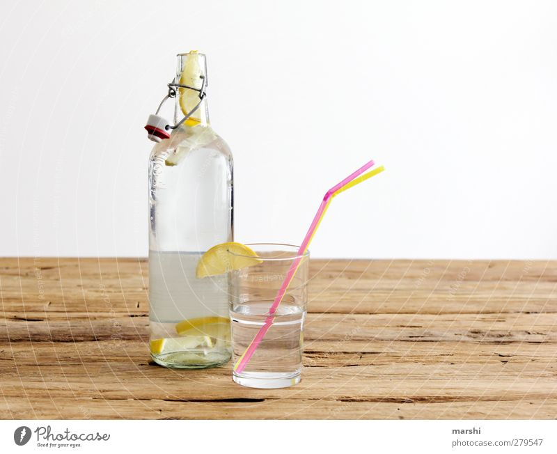 lemonade Beverage Drinking Cold drink Lemonade Bottle Glass Yellow Fruit Fruity Refreshment Blade of grass Thirst-quencher Water Wooden table Colour photo