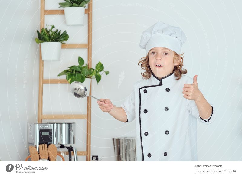 Boy in cook hat holding ladle and showing thumb up in kitchen Cook Boy (child) Kitchen Ladle chef Child Hat Cool (slang) Gesture Cooking Metal Modern Home