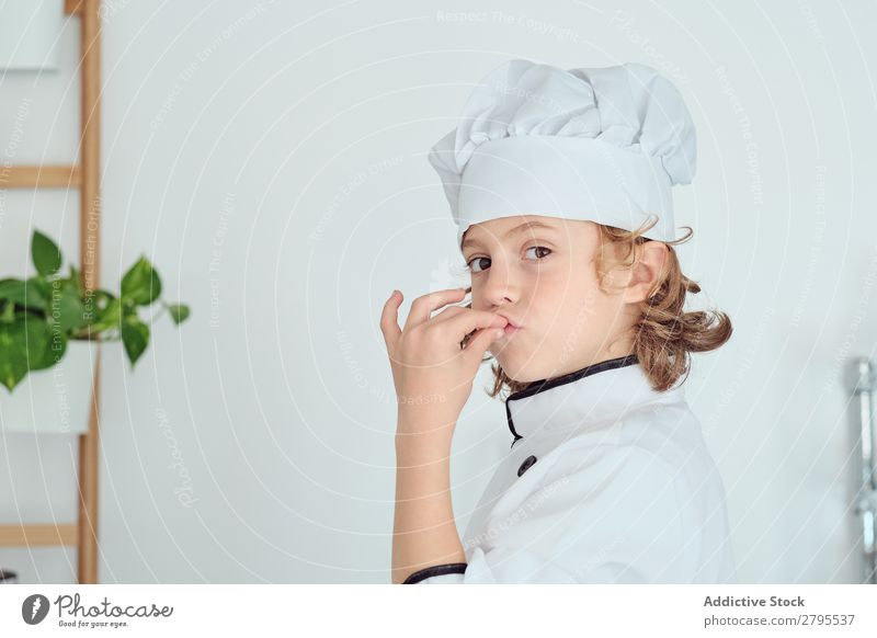 Boy in cook hat showing delicious gesture in kitchen Cook Boy (child) Kitchen Delicious chef Child Hat Cool (slang) Gesture Cooking Modern Home Gourmet Indicate