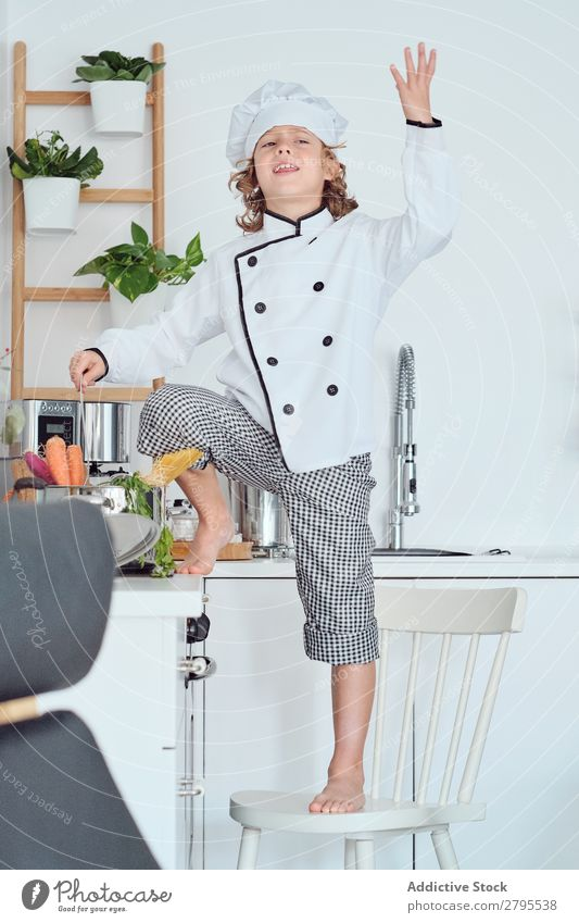 Boy in cook hat with upped hand near pot on chair in kitchen Cook Boy (child) Pot Hand Kitchen Chair chef Child Vegetable Hat Cooking Modern Funny Home Light