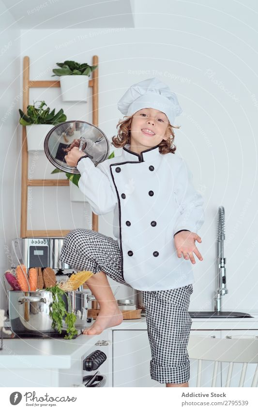 Boy in cook hat with cover near pot on chair in kitchen Cook Boy (child) Pot Cover Kitchen Chair chef Child Vegetable Hat Cooking Modern Funny Home Light