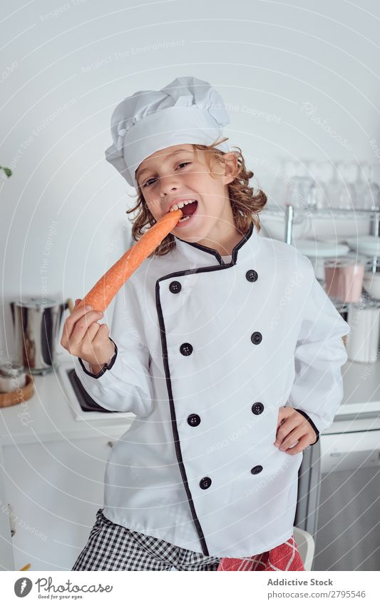 Boy in cook hat with carrot in kitchen Cook Boy (child) Kitchen Carrot chef Child Vegetable Hat Fresh Indicate Hand Hip Cooking Modern Funny Home Light