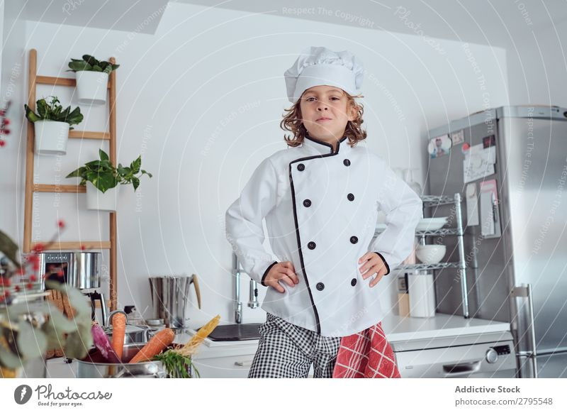 Boy in cook hat in kitchen Cook Boy (child) Kitchen Carrot chef Child Vegetable Hat Fresh Indicate Hand Hip Cooking Modern Funny Home Light preparing Happiness