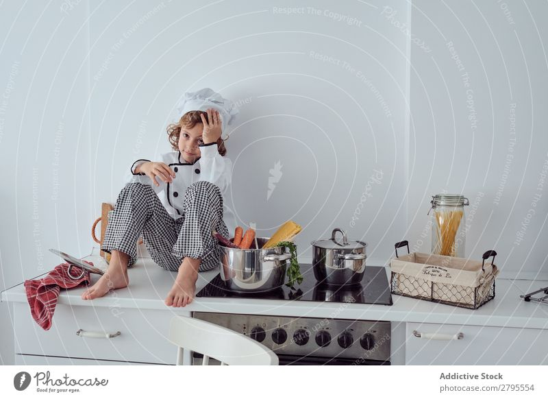Boy in cook hat sitting near pots on electric fryer in kitchen Cook Boy (child) Pot Kitchen chef Child Vegetable Hat Stove & Oven Cooking Modern Funny Home