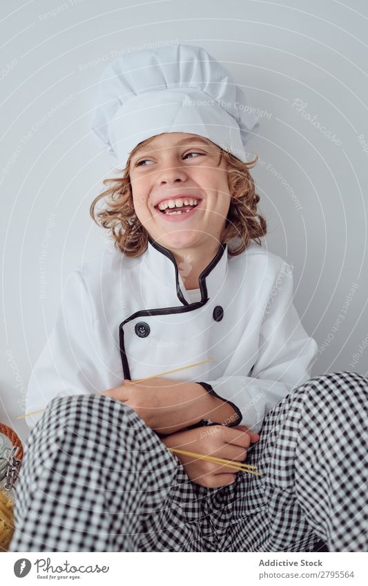 Boy sitting near pots on electric fryer in kitchen Cook Boy (child) Pot Kitchen chef Child Vegetable Hat Stove & Oven Cooking Modern Funny Home Light preparing