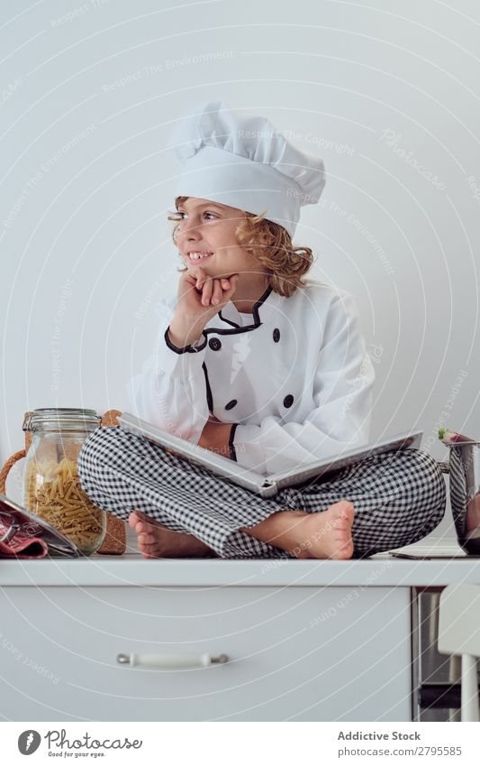 Boy in cook hat with book sitting near pots on electric fryer in kitchen Cook Boy (child) Book Pot Kitchen chef Child Vegetable Hat Volume Reading Stove & Oven