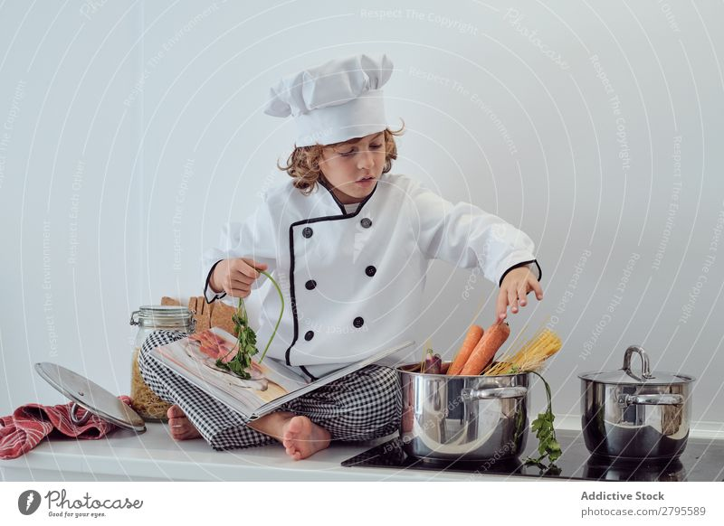 Boy in cook hat putting pasta in pot on electric fryer in kitchen Cook Boy (child) Pot Pasta Kitchen chef Child Macaroni Carrot Vegetable Hat Stove & Oven Putt