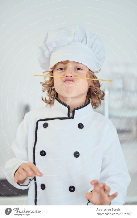 Boy in cook hat making moustache of macaroni in kitchen Cook Boy (child) Kitchen Moustache Macaroni chef Child Hat Pasta Dry Make Cooking Modern Funny Home