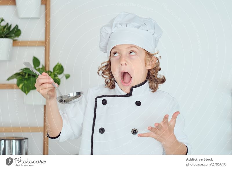 Boy in cook hat holding ladle near mouth in kitchen Cook Boy (child) Kitchen Ladle Mouth chef Child Pot tasting Food Hat Cooking Metal Modern Home Light