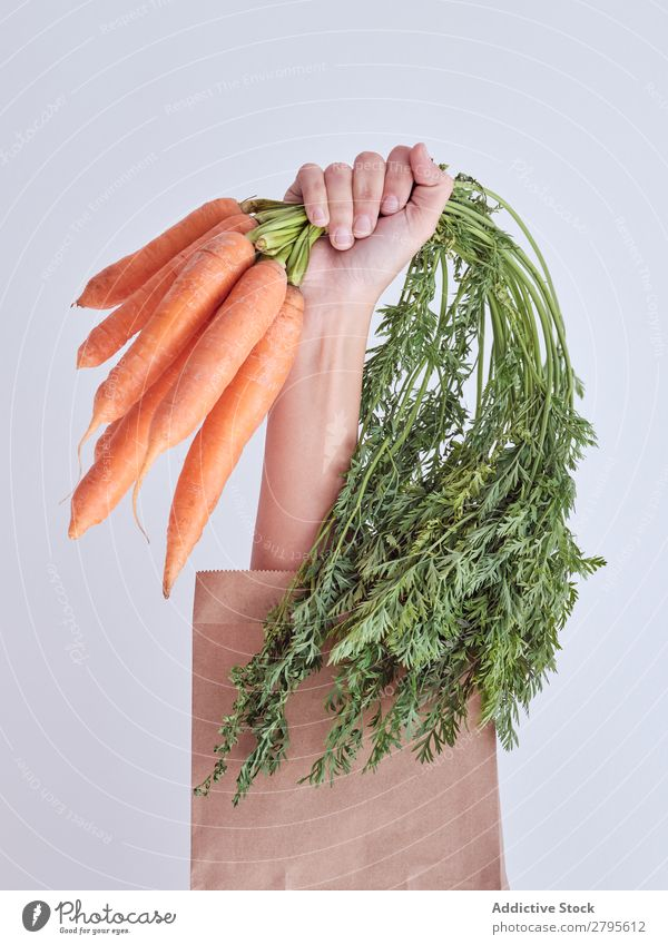 Person hand reached out from packet and holding carrots Human being Hand Carrot Package Vegetable Food Bag Craft (trade) Paper Conceptual design Fresh Markets