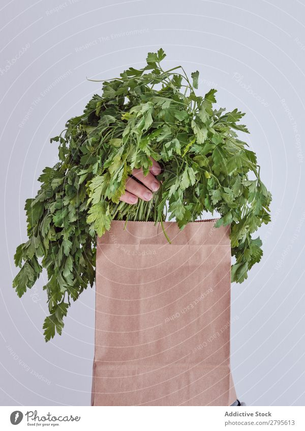 Person hand reached out from packet and holding parsley Human being Hand Package Vegetable Food Bag Craft (trade) Paper Conceptual design Fresh Markets Healthy