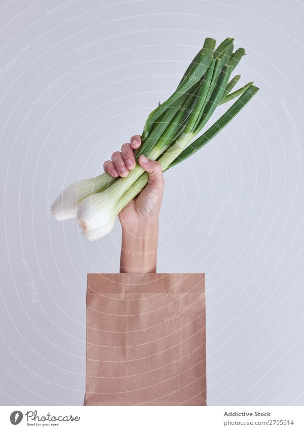 Person hand reached out from packet and holding leek Human being Hand Package Vegetable Food Bag Craft (trade) Paper Conceptual design Fresh Markets Healthy