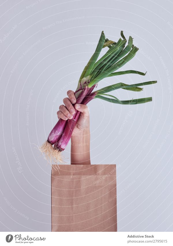 Person hand reached out from packet and holding red leek Human being Hand Package Vegetable Food Bag Craft (trade) Paper Conceptual design Fresh Markets Healthy