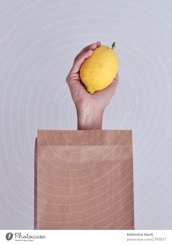 Person hand reached out from packet and holding lemon Human being Hand Carrot Package Vegetable Food Bag Craft (trade) Paper Conceptual design Fresh Markets