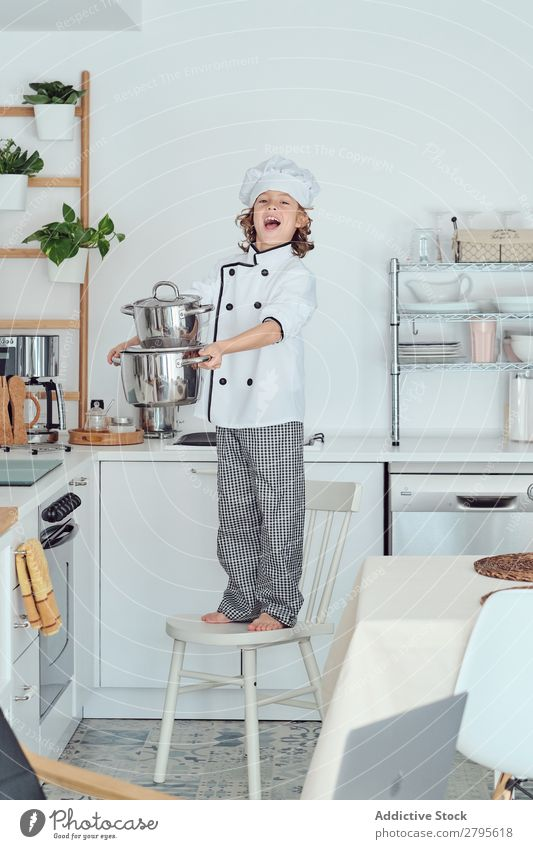 Smiling boy in cook hat holding pots on chair in kitchen Cook Boy (child) Pot Kitchen Chair chef Child Hat Cooking Modern Home Happy Light preparing Happiness