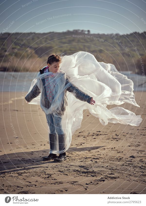 Girl entangled in plastic on river coast Plastic textile waving River Coast Side Wind Sand Water Mountain Landscape Beach Help White Sun Woman Joy Happiness