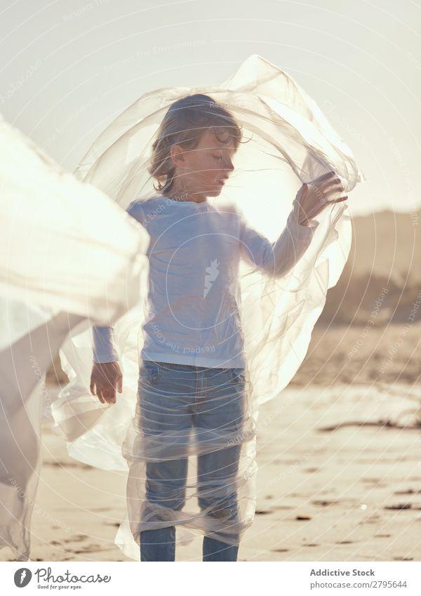Child entangled in plastic on river coast Boy (child) Plastic textile waving River Coast Side Wind Sand Water Mountain Landscape Beach Help White Sun Joy