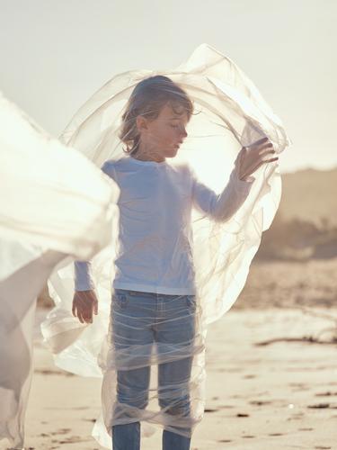 Child entangled in plastic on river coast Boy (child) Plastic River Coast Side Wind