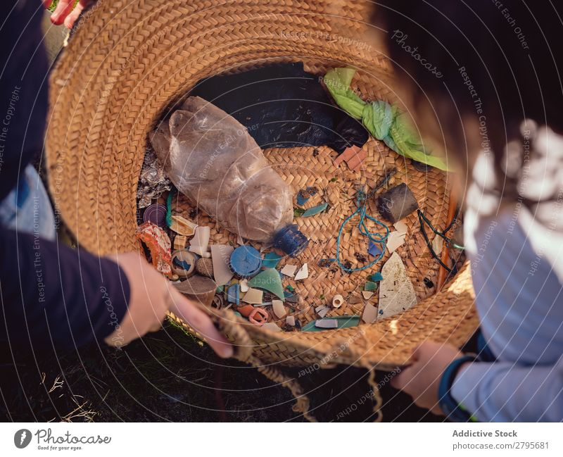 Person and children with heaps of garbage in hands near basket Trash container Heap Hand Basket Child Human being Accumulation Container